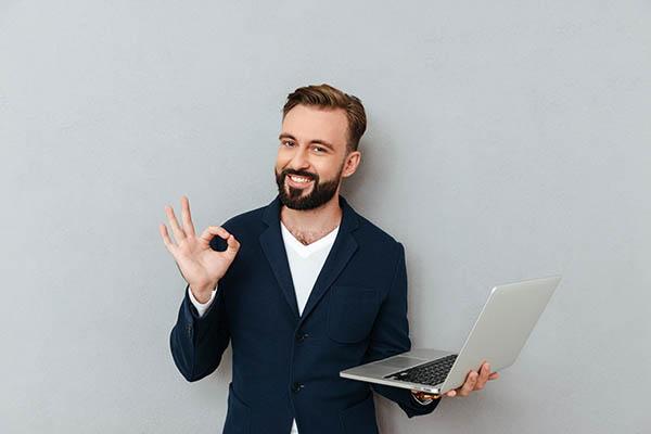 Hombre joven y alegre con traje mirando a la cámara mientras sostiene un ordenador portátil.